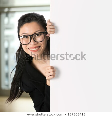 Young girl peering around the edge of a sign Stock photo © stryjek