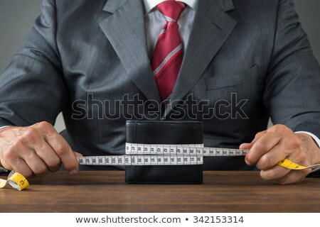 Businessman Wrapping Wallet With Measuring Tape Stock photo © AndreyPopov