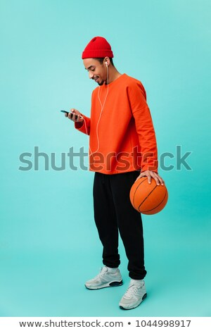 portrait of african sporty man in uniform holding basketball ball Stock photo © LightFieldStudios