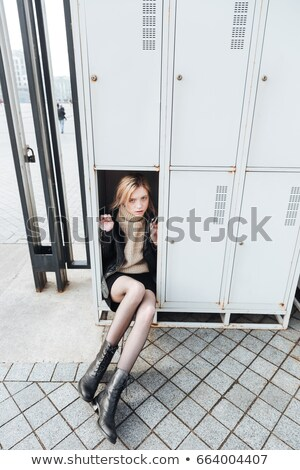 Serious young blonde lady sitting in safe Stock photo © deandrobot