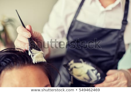 Woman hairdresser applying dye to man hair Stock photo © Elnur