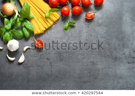 black uncooked pasta with tomato and basil stock photo © furmanphoto