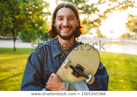 smiling young guy spending time at the skate park stock photo © deandrobot