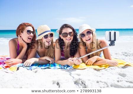 women with selfie stick and smartphone on beach Stock photo © dolgachov