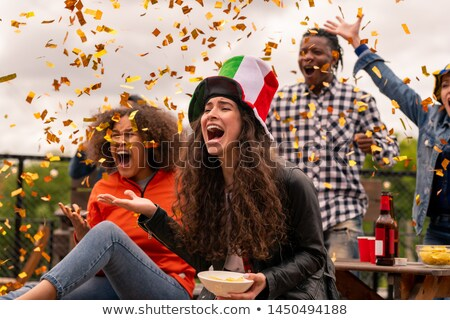 Two shouting female football fans and their friends throwing confetti Stock photo © pressmaster