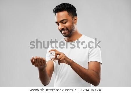 happy indian man with perfume over gray background Stock photo © dolgachov