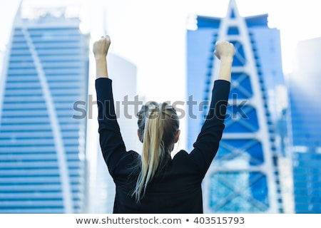 Young beautiful woman hand high over a blue sky Stock photo © Lopolo