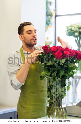 florist or seller setting red roses at flower shop Stock photo © dolgachov