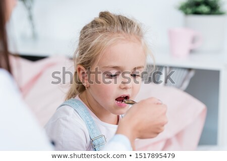 Sick little blond girl taking medicine from spoon held by her doctor in hospital Stock photo © pressmaster