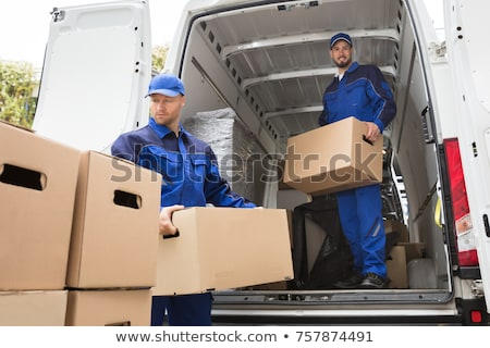 Two Young Male Movers Carrying Cardboard Boxes From Truck Stock photo © AndreyPopov