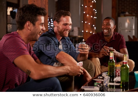 friends playing cards game at home in evening Stock photo © dolgachov