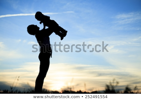 Mother holding baby up in the back lit, Stock photo © Lopolo