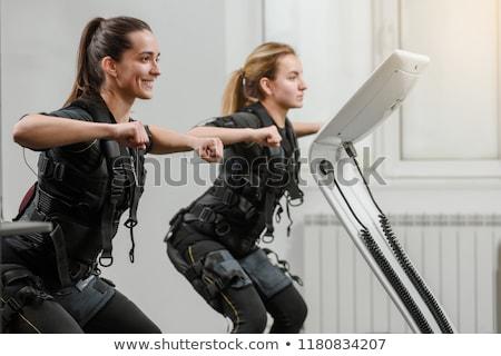 Woman stretching in the EMS gym Stock photo © Kzenon