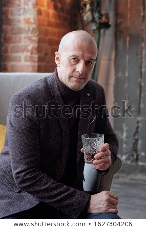 Bald businessman with glass of hard liquor Stock photo © pressmaster