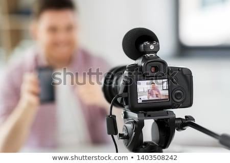 male blogger with smartphone videoblogging at home stock photo © dolgachov
