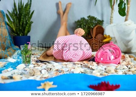 The girls is lying on a fictional beach near the sea or ocean, sunbathes. Stock photo © Illia