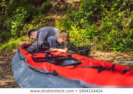 Father and son prepare a kayak for rowing on the sea Stock photo © galitskaya