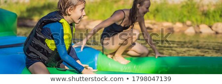 Mother and son go through an inflatable obstacle course in the pool BANNER, LONG FORMAT Stock photo © galitskaya