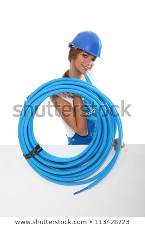 portrait of cute female plumber carrying hose with copyspace against studio background stock photo © photography33