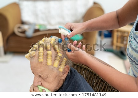 Elderly lady using hair rollers Stock photo © photography33