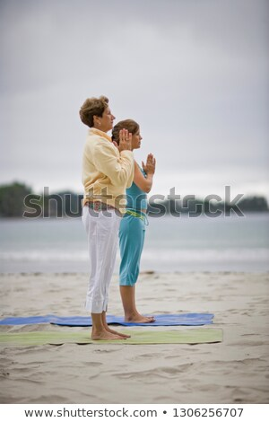 Beach Yoga with Young Women with Shoreline - vertical Stock photo © Schmedia