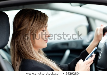 Beautiful businesswoman sending a text while driving to work Stock photo © wavebreak_media