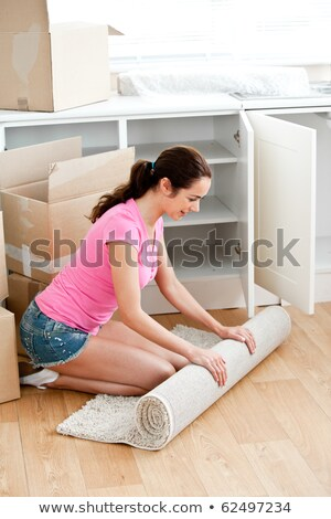 Happy woman roll a carpet out in her new house Stock photo © wavebreak_media