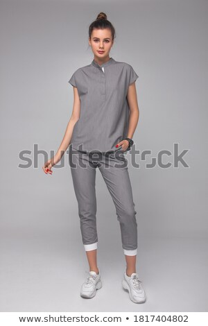 Businesswoman Standing On One Leg With Hands On Wall Stock photo © Maridav