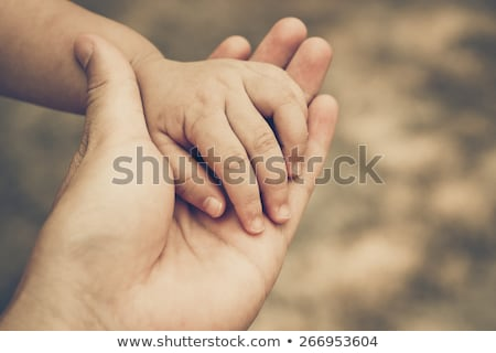 african childs hand holding a white adults hand stock photo © thisboy
