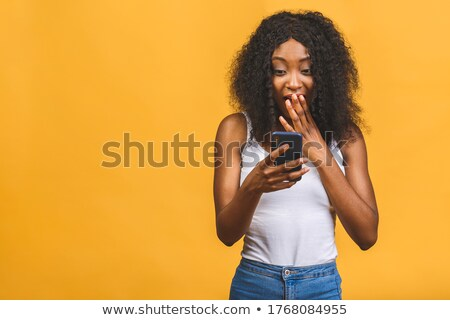 Woman smiling as she reads an sms Stock photo © dash