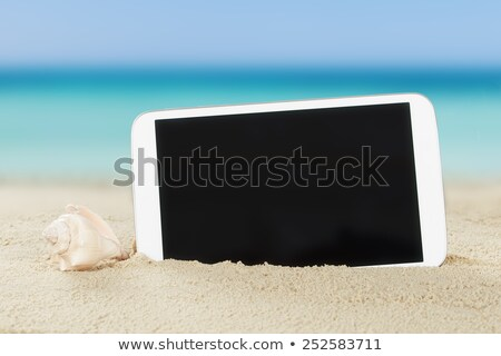 tablet computer and shell on sand stock photo © andreypopov
