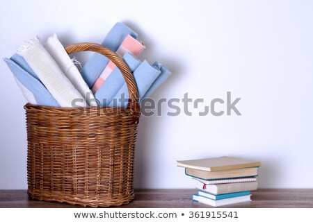 Rugs in Basket and Piled Books Against White Wall Stock photo © ozgur
