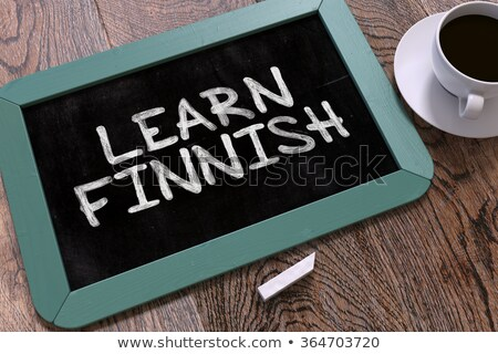 Learn Finnish Handwritten by white Chalk on a Blackboard. Stock photo © tashatuvango
