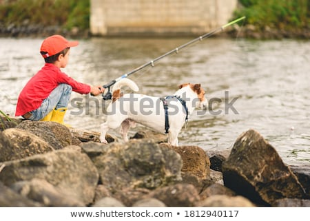 Foto d'archivio: Boy Fishing With His Dog