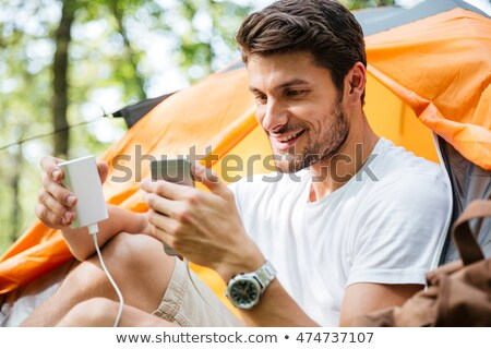Happy man tourist charging battery of mobile phone in forest Stock photo © deandrobot