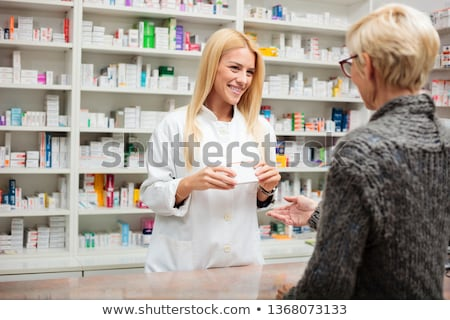 Pharmacist woman with medicine at counter in pharmacy Stock photo © vectorikart