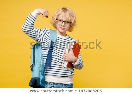 strong male child showing muscles in classroom at lesson stock photo © diego_cervo
