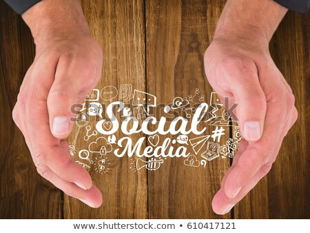 Stock photo: Hands around white social media doodles against wood