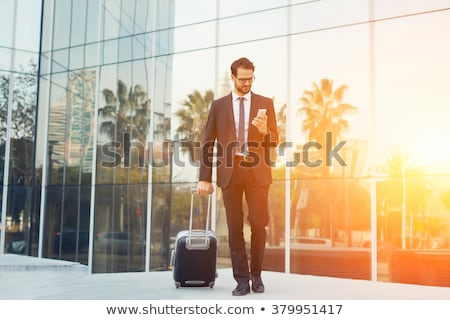 Man outdoors with suitcase using cellular phone Stock photo © monkey_business