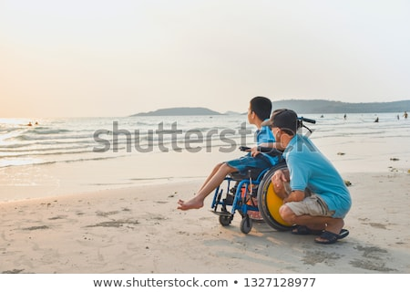 Disabled young man sitting in a wheelchair and looks at the sea  Stock photo © manaemedia