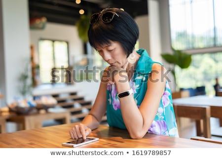 азиатских женщину Smart Смотреть телефон домой Сток-фото © wavebreak_media