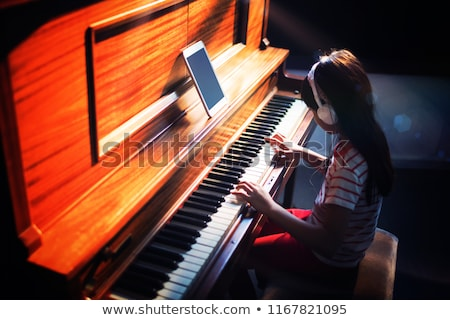 High angle view of concentrated girl wearing headphones while practicing piano in classroom at music Stock photo © wavebreak_media