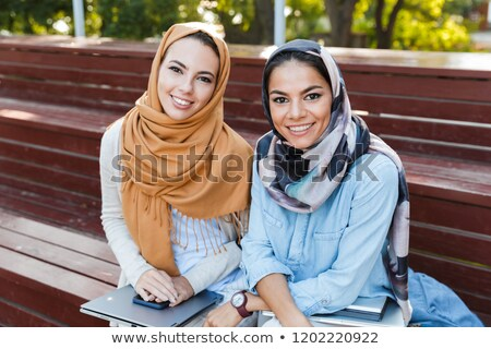 Muslim young woman walking outdoors holding books. Stock photo © deandrobot