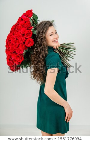 Gorgeous woman in red dress keeping bouquet of roses Stock photo © studiolucky