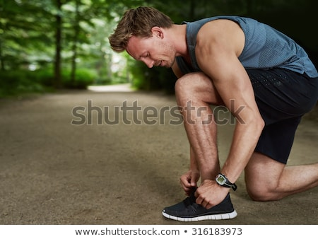 Concentrated young sportsman tying shoelaces Stock photo © deandrobot