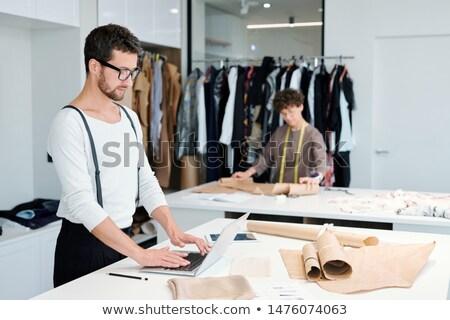 Fiatal szabó áll asztal laptop szörfözik Stock fotó © pressmaster