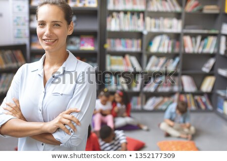 Front view of a happy teacher crossing arms while his pupils relaxing themselves over digital tablet Stock photo © wavebreak_media