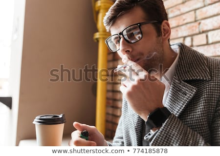 young businessman smoking cigarette stock photo © stockyimages
