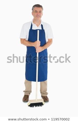 Man in blue apron holding sweeping brush stock photo © wavebreak_media