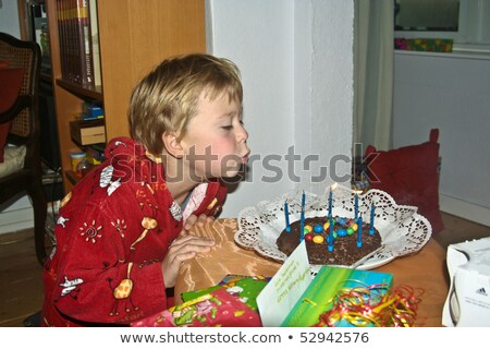 boy blows down his birthday candles Stock photo © meinzahn